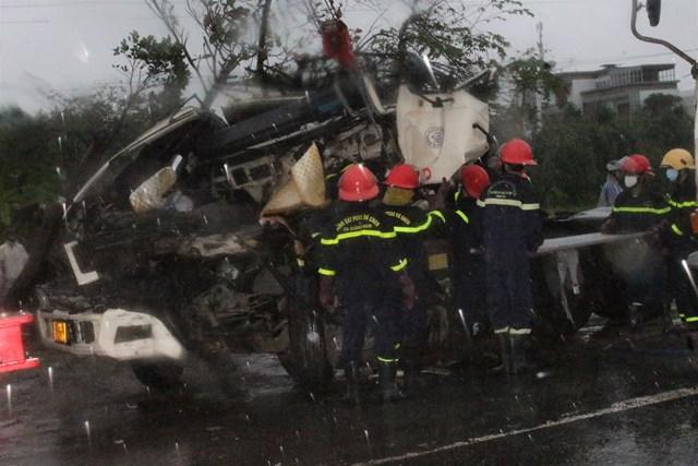 Lực lượng chức năng đang đưa thi thể tài xế xe đầu kéo ra khỏi xe.