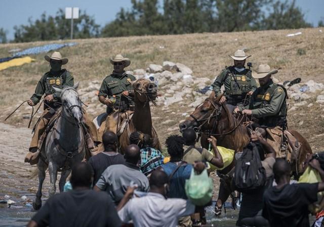 Các quan chức tại biên giới Mỹ cố gắng kiểm soát tình hình tại nơi người di cư Haiti đang tạm trú. Ảnh AP