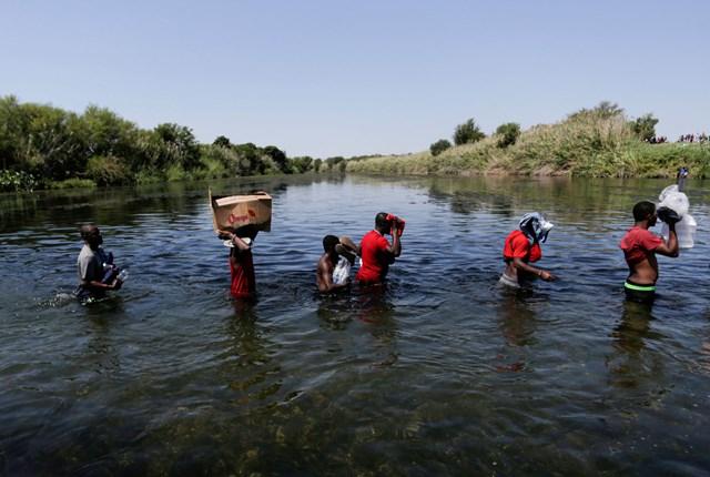 Người di cư Haiti mạo hiểm vượt sang biên giới Mexico để tìm kiếm nguồn thực phẩm. Ảnh Reuters