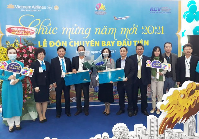 Lãnh đạo Sở Du lịch Đà Nẵng, Cảng hàng không quốc tế Đà Nẵng và Vietnam Airlines trao quà tặng may mắn cho 2 khách đầu tiên của năm 2021. Ảnh Thanh Tùng.