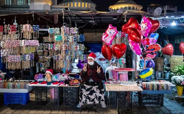 Một phụ nữ bán hàng rong làm dấu hiệu V (chiến thắng) trên Quảng trường Taksim ở Istanbul trong lễ đón năm mới ở Istanbul, Thổ Nhĩ Kỳ.