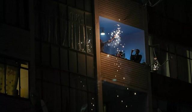 Người dân Nam Phi đón năm mới 2021 trên ban công tòa nhà khi lệnh giới nghiêm vào ban đêm được áp dụng lại trong bối cảnh bùng phát mạnh mẽ dịch bệnh Covid-19 trên toàn quốc.