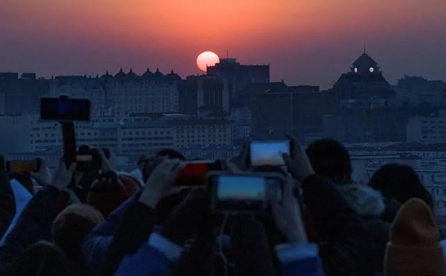 Người dân thành phố Bắc Kinh, Trung Quốc chụp ảnh mặt trời mọc đầu tiên của năm mới sau đợt bùng phát dịch bệnh Covid-19.