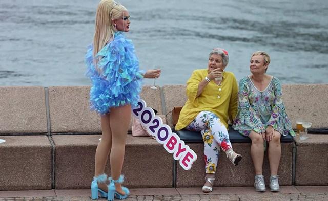 """Một người vui chơi cầm tấm biển ghi """"2020BYE"""" khi một số ít người bắt đầu đón giao thừa tại bờ sông Cảng Sydney trong bối cảnh các quy định phòng chống Covid-19 được thắt chặt ở Sydney, Úc."""