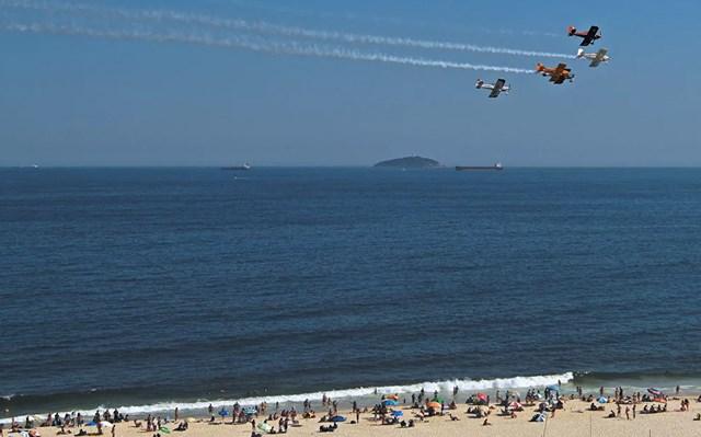 Máy bay trình diễn vẽ khói cho mọi người trên bãi biển Copacabana, Rio de Janeiro, Brazil. Bãi biển đêm giao thừa hàng năm của thành phố Rio de Janeiro và màn bắn pháo hoa công phu đã bị hủy do đại dịch Covid-19 hoành hành.