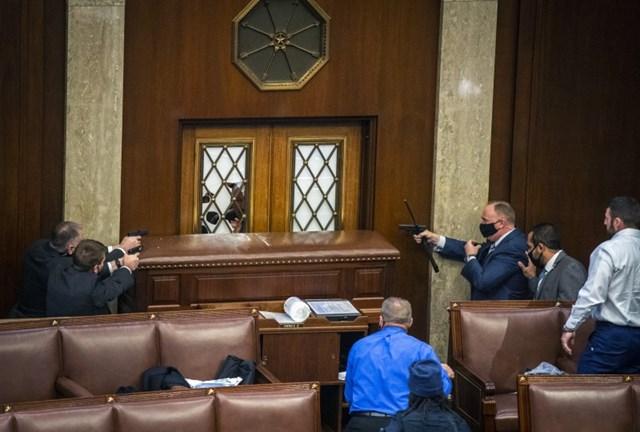 Lực lượng an ninh bảo vệ các nhà lập pháp từ bên trong tòa nhà.Ảnh: Washington Post.