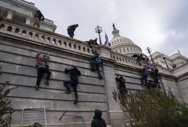 Cơn thịnh nộ lên cao trào khi những người biểu tình bắt đầu trèo vào tòa nhà Quốc hội Mỹ. Ảnh: Washington Post.