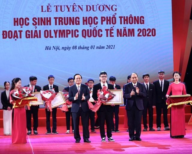 Thủ tướng Nguyễn Xuân Phúc, Chủ tịch Hội đồng Thi đua - Khen thưởng Trung ương và Bộ trưởng Bộ GDĐT Phùng Xuân Nhạ trao Huân chương Lao động cho các em học sinh THPT đoạt giải Olympic quốc tế 2020.