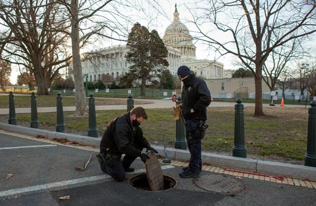 Các sĩ quan cảnh sáttừ Bộ phận Thiết bị nguy hiểm của Cảnh sát Điện Capitol Mỹ kiểm tra và niêm phong một miệng cống trong khuôn viên công trình.