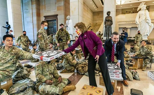 Các Hạ nghị sĩ Vicky Hartzler và Michael Waltz đưa pizza cho các thành viên của Lực lượng Vệ binh Quốc gia tập trung tại sảnh dành cho khách tại Điện Capitol, khi Hạ viện tiếp tục với cuộc bỏ phiếu gấp gáp để luận tội Tổng thống Donald Trump.