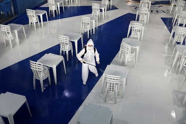Công nhân khử trùng trụ sở của trường Samba Portela của Brazil.