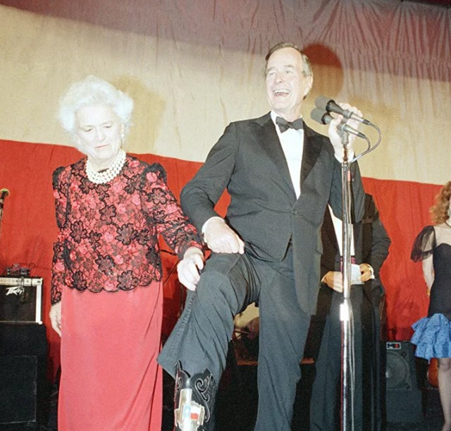 Đệ nhất phu nhân Barbara Bush giúp chồng mình, Tổng thống George Bush, giới thiêu một chiếc ủng có biểu tượng của tiểu bang Texas trong buổi tiệc chiêu đãi ở Washington, ngày 21/1/1989.