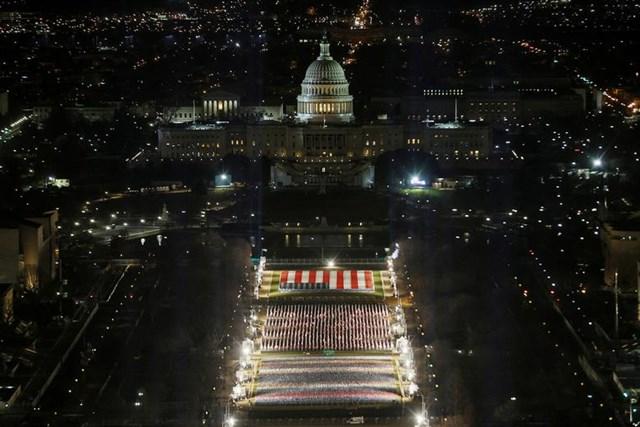 """""""Cánh đồng cờ"""" được chiếu sáng trên National Mall khi Tòa nhà Quốc hội Hoa Kỳ được chuẩn bị cho lễ nhậm chức của Tổng thống đắc cử Joe Biden. Ảnh: Reuters."""