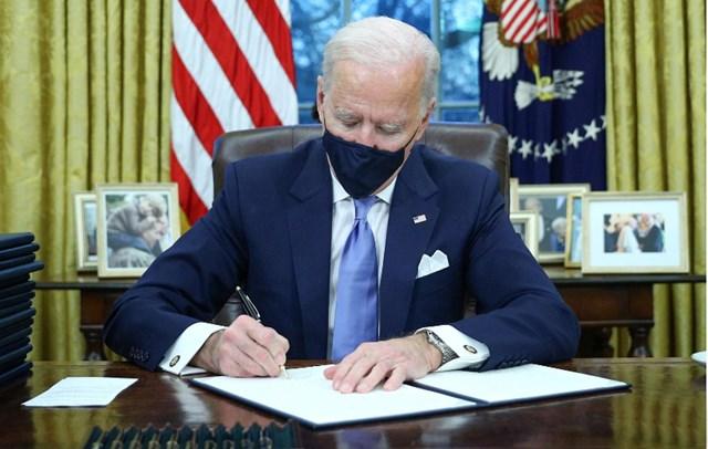 Tổng thống Biden trong ngày làm việc đầu tiên tại Phòng Bầu dục. Ảnh: Reuters.