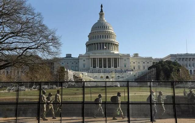 Lực lượng Vệ binh Quốc gia đi dọc hàng rào bảo vệ quanh Điện Capitol Mỹ. Ảnh: Reuters.