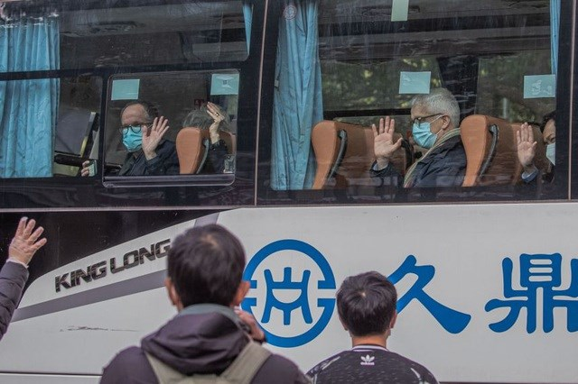 Các chuyên gia lên ô tô rời khách sạn cách ly ở Vũ Hán, trung Quốc. Ảnh: Reuters.