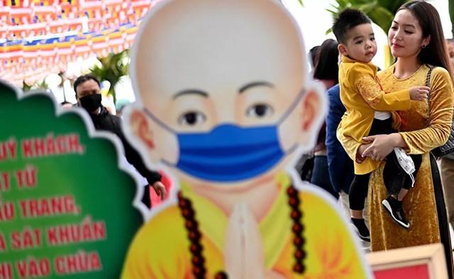 Một phụ nữ Việt Nam bế con đi lễ tại chùa Trấn Quốc, một trong những ngôi chùa cổ nhất ở Hà Nội.