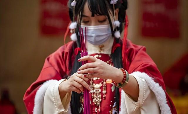 Một người phụ nữ mặc trang phục truyền thống thắp hương và cầu nguyện tại đền Ma Zhu Miao tại khu phố Tàu của Yokohama, Nhật Bản.