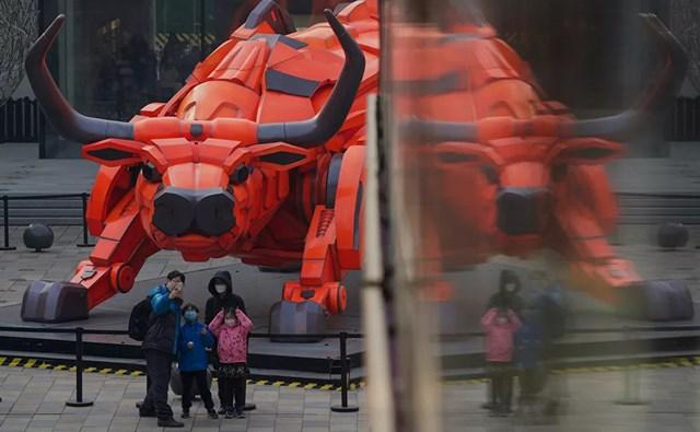Một gia đình chụp ảnh trước bức tượng điêu khắc bò tót tại một trung tâm thương mại ở Bắc Kinh.