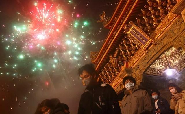 Người dân xem pháo hoa trong đêm Giao thừa nhưng vẫn đeo khẩu trang phòng dịch Covid-19 ở Đài Bắc, Đài Loan (Trung Quốc).