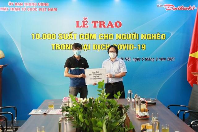 Quyền Tổng Biên tập Lê Anh Đạt nhận bảng tượng trưng tiền hỗ trợ chương trình từ bạn đọc báo Đại Đoàn Kết. Ảnh: Quang Vinh.