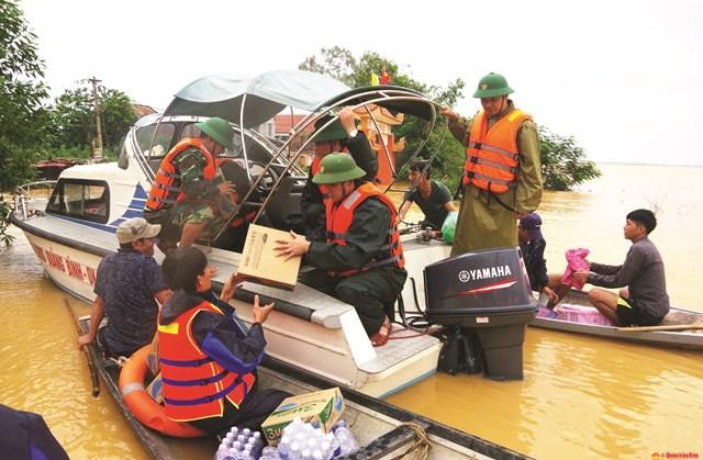 Cán bộ, chiến sĩ Ban Chỉ huy quân sự huyện Quảng Ninh (Quảng Bình) vượt lũ hỗ trợ lương thực cho người dân xã Tân Ninh.