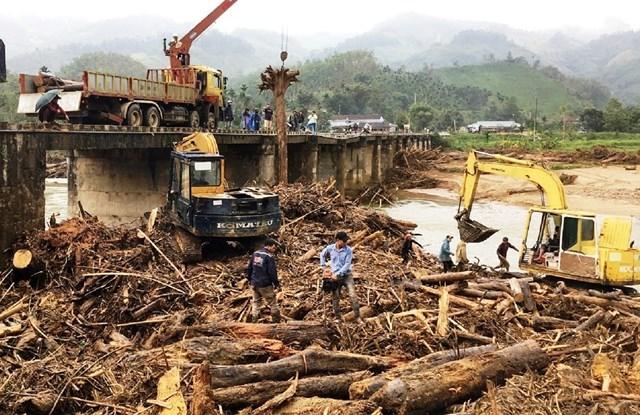 Lũ lớn cuốn theo hàng trăm m3 gỗ từ thượng nguồn trôi về nằm dày đặc lấp kín chân cầu Nước Bua, ở xã Sơn Bua, huyện Sơn Tây, tỉnh Quảng Ngãi.