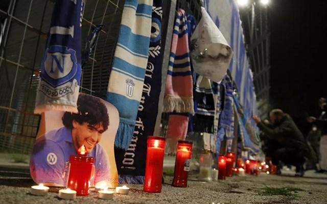 Người hâm mộ treo khăn và thắp nến viếng Maradona. Ảnh: AP.