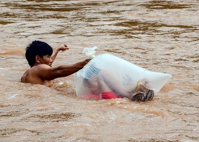 Nhiều vụ việc chỉ được cơ quan chức năng vào cuộc khi truyền thông vào cuộc, dư luận lên tiếng. Trong ảnh: Học sinh ở bản Huổi Hạ (Na Sang, Mường Chà, Điện Biên) phải chui túi nilon nhờ người lớn đưa qua suối để tới trường.