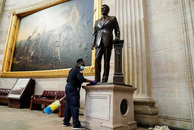 Một công nhân làm vệ sinh bức tượng cựu Tổng thống Ronald Reagan. Ảnh: Reuters.