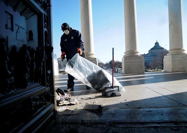 Một công nhân dọn dẹp các mảnh vỡ bên ngoài điện Capitol, một ngày sau khi những người ủng hộ Tổng thống Trump xông vào tòa nhà. Ảnh: Reuters.