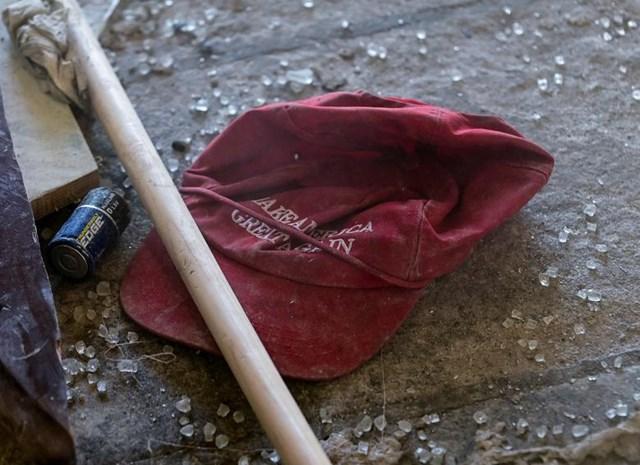 """Một chiếc mũ in khẩu hiệu """"Làm cho nước Mỹ vĩ đại trở lại"""" nằm trong đống đổ nát bị bỏ lại ở trạm kiểm soát lối vào. Ảnh: Reuters."""