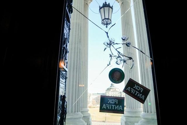 Các lỗ đạn và hình dán trên lối vào điện Capitol. Ảnh: Reuters.