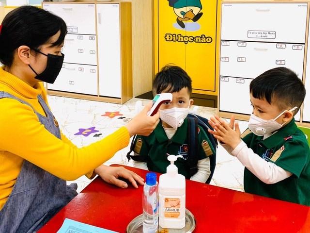 Học sinh mầm non ở Hà Nội đo nhiệt độ và khử khuẩn tay trước khi vào lớp.