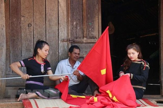 Người dân may cờ chào mừng Đại hội lần thứ XIII của Đảng.