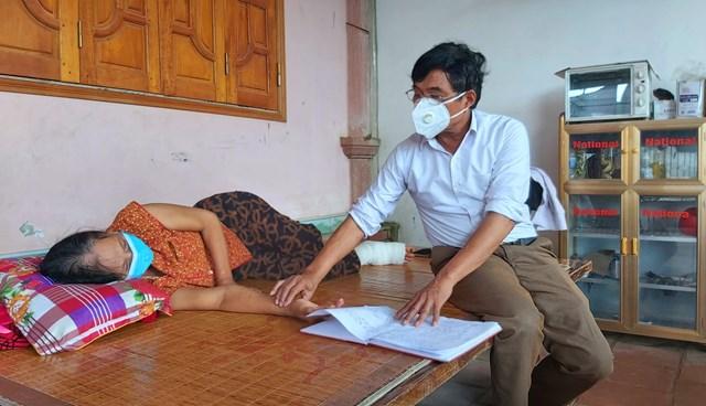 Lương y Bùi Đức Lục khám lại vết thương rắn độc cắn cho bệnh nhân Nguyễn Thị Thảo.