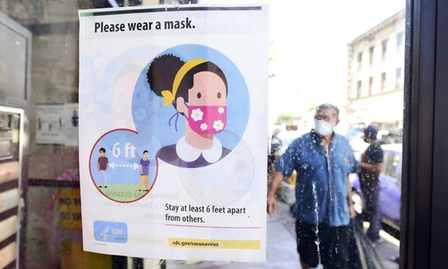 Bảng nhắc nhở người dân đeo khẩu trang, giữ khoảng cách tại bang California, Mỹ, hôm 19/7. Ảnh: AFP.