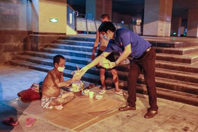 Ông Nguyễn Hồng Toàn xúc động nhận phần cơm của Báo Đại Đoàn Kết trao.