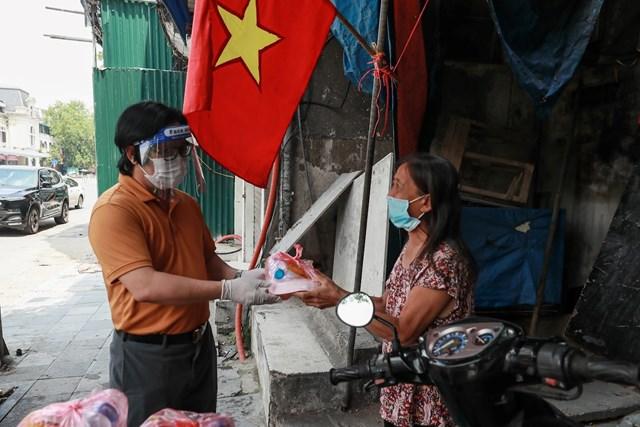 Quyền Tổng Biên tập Báo Đại Đoàn Kết Lê Anh Đạt trao suất ăn cho người nghèo.