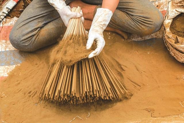 Công đoạn nhúng hương vào nước keo rồi lăn tẩm với hỗn hợp mùn cưa và bột trầm.