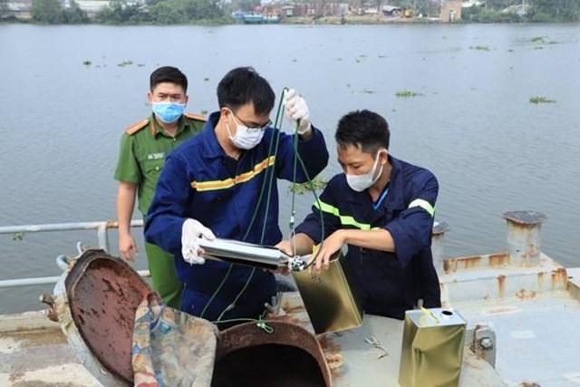 Công an lấy mẫu xăng trên phương tiện thủy các đối tượng đang vận chuyển. Ảnh: CAĐN