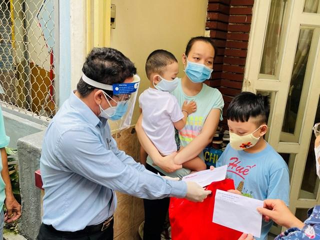 Nhà báo Chu Ninh, Trưởng Ban đại diện Báo Đại Đoàn kết tại TP HCM trao quà tặng cháu Bùi Nhật Quang Đăng. Ảnh: Hữu Vinh.