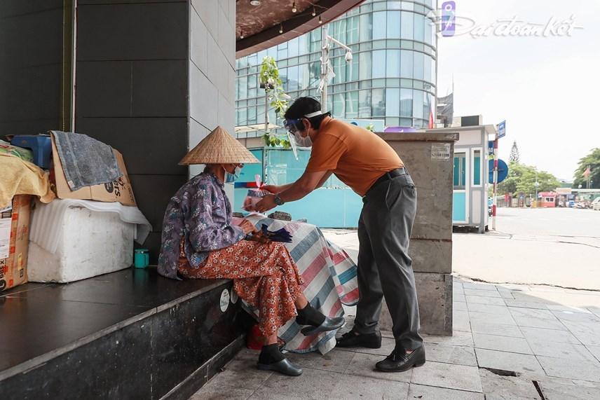 Báo Đại Đoàn Kết trao suất cơm cho một cụ già vô gia cư tại khu vực ga Hà Nội. Ảnh: Quang Vinh.