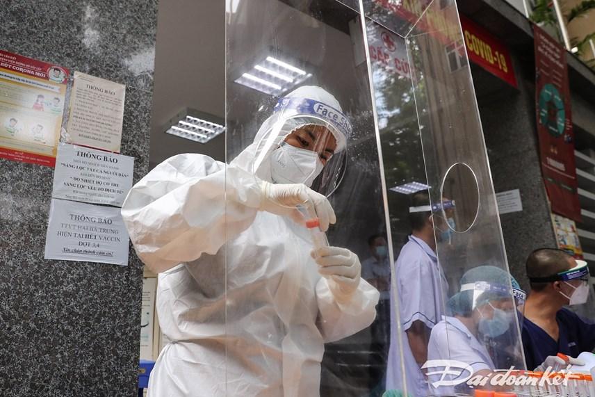 Sau khi lấy mẫu, cán bộ y tế cho vào từng hộp đựng mẫu, ghi rõ tên của từng trường hợp. Ảnh: Quang Vinh.