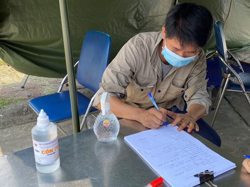 Nhân viên y tế giúp người dân khai báo y tế, thực hiện đo nhiệt độ. Ảnh: L.A..