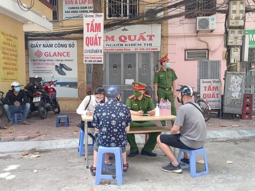 Lực lượng chức năng yêu cầu người dân khai báo thông tin tại chốt kiểm soát khu vực vườn hoa1/6(phường Quang Trung, quận Đống Đa).