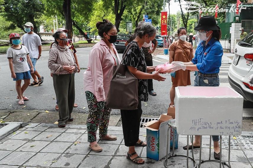 Báo Đại Đoàn Kết và nhóm tình nguyện phát suất ăn cho những hoàn cảnh khó khăn, những người vô gia cư. Ảnh: Quang Vinh.