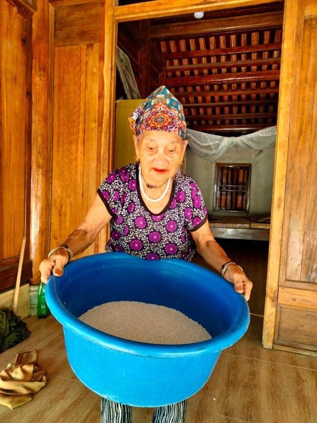 Cụ Vi Thị Mão đưa chậu gạo nặng 10kg đến tay cán bộ Mặt trận để ủng hộ chống dịch.