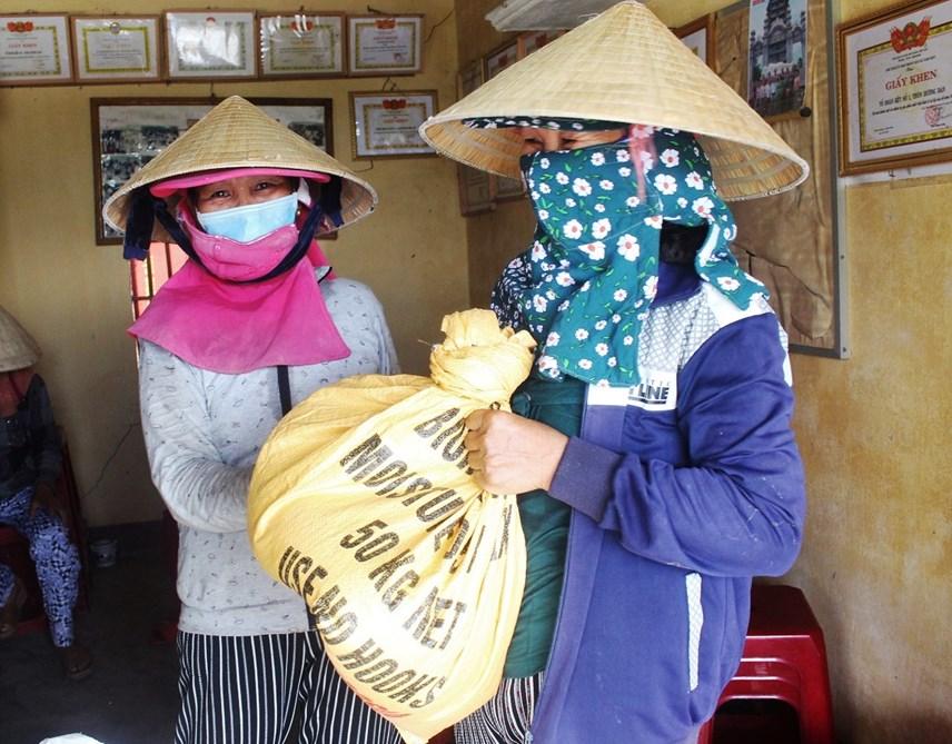 Những cụ già đem từng bao gạo ủng hộ.