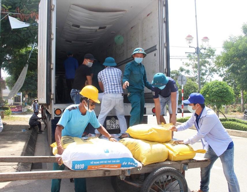 Người dân bốc hàng hóa lên xe để vận chuyển vào TP HCM.